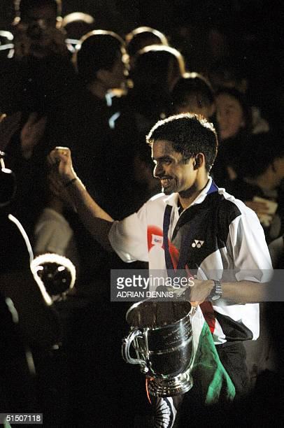 India's Pullela Gopichand does a lap of honour with the Silver Challenge Trophy after winning the final mens single match against China's Chen Hong...