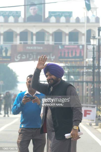 India's Punjab cabinet minister and former cricketer Navjot Singh Sidhu gestures before crossing into Pakistan at the border crossing in Wagah about...