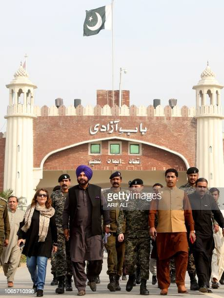 India's Punjab cabinet minister and former cricketer Navjot Singh Sidhu walks after entering Pakistan from India at the border crossing in Wagah on...
