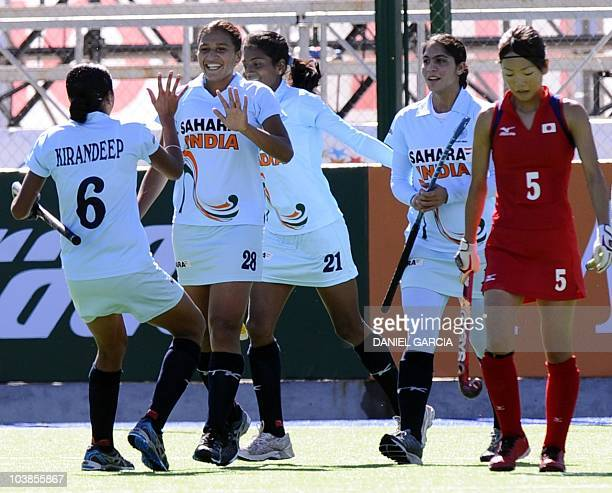 India's Rani Rampal celebrates with teammates after she scored the first goal against Japan during the field hockey Group A match for the Women World...