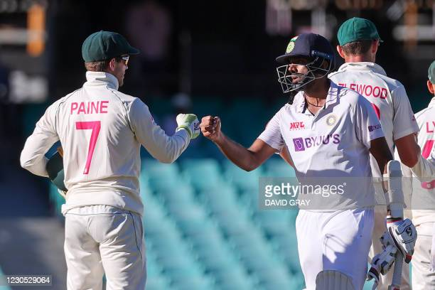 India's Ravichandran Ashwin fist bumps with Australia's captain Tim Paine at the end of the third cricket Test match between Australia and India at...