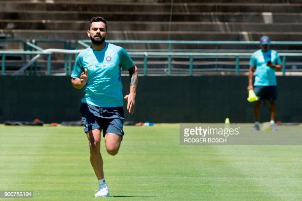 India's right handed batsman and captain Virat Kohli runs during a training session at the Newlands Cricket ground on January 3 in Cape Town prior to...
