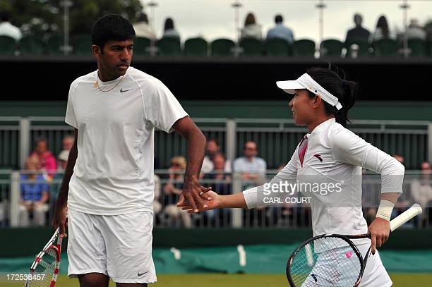 India's Rohan Bopanna and his partner China's Zheng Jie touch hands between points against Sweden's Johan Brunstrom and Hungary's Katalin Marosi in...
