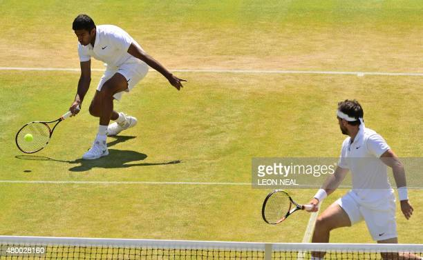 India's Rohan Bopanna returns as his partner Romania's Florin Mergea stands ready at the net between points against Netherlands' JeanJulien Rojer and...