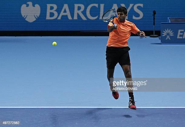 India's Rohan Bopanna returns the ball to US player Bob Bryan and US player Mike Bryan during his men's doubles group stage match with Romania's...