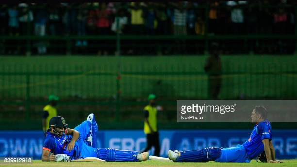 India's Rohit Sharma and MS Dhoni lay on the ground after a tense situation arose following some spectators throwing plastic bottles in the playing...