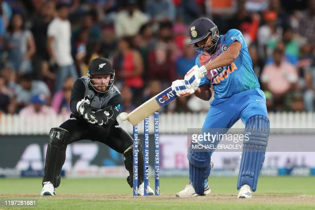 Indias Rohit Sharma bats watched by New Zealands Tim Seifert during the third Twenty20 cricket match between New Zealand and India at Seddon Park in...