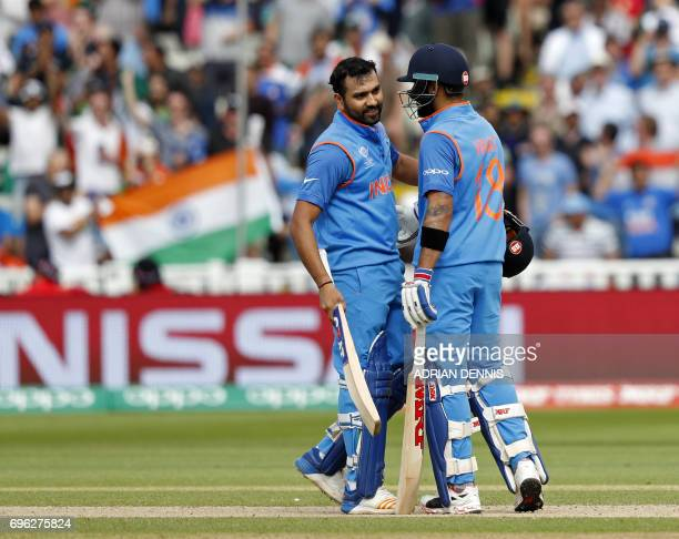 India's Rohit Sharma talks with his batting partner India's captain Virat Kohli after Sharma reached his century during the ICC Champions Trophy...