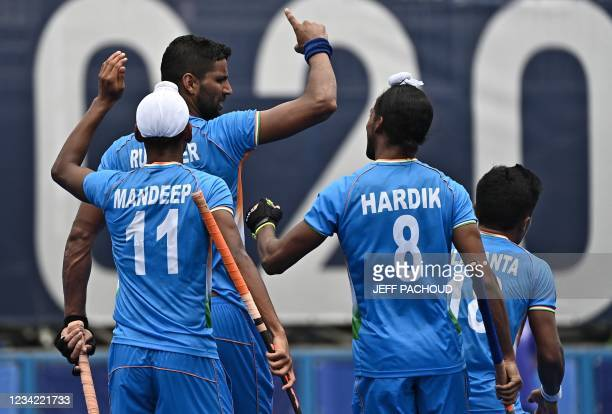 India's Rupinder Pal Singh celebrates with teammates after scoring against Spain during their men's pool A match of the Tokyo 2020 Olympic Games...