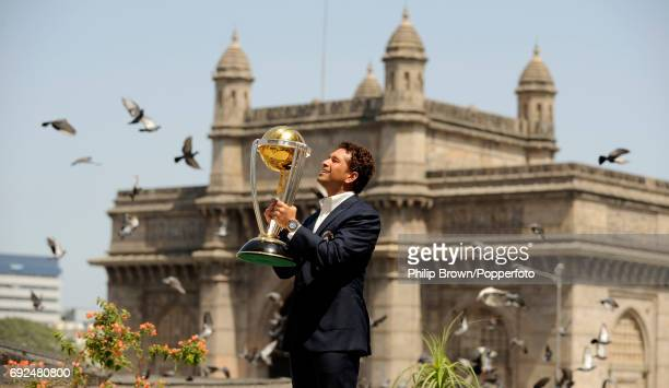 India's Sachin Tendulkar stands on a roof at the Taj Hotel in Mumbai holding the Cricket World Cup trophy after defeating Sri Lanka in the final with...