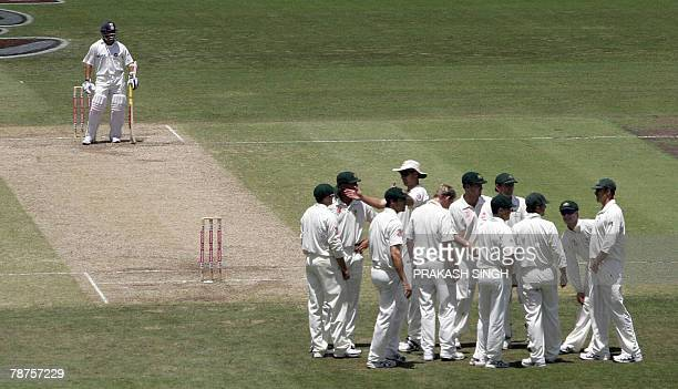 India's Sachin Tendulkar waits as Australia cricketers celebrate for the wicket of India's Yuvraj Singh, on day three of the second test match...
