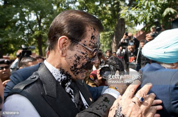 India's Sahara group chairman Subrata Roy 's face is covered in black ink as he arrives at the Supreme Court in New Delhi on March 4 2014 Ink was...
