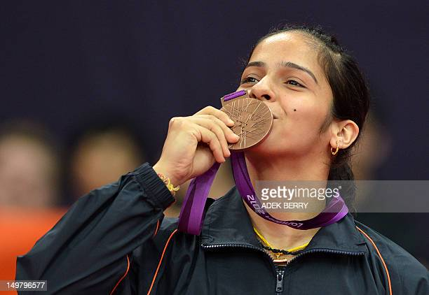 India's Saina Nehwal kisses her bronze medal after beating China's Wang Xin in their bronze medal women's singles badminton match at the London 2012...