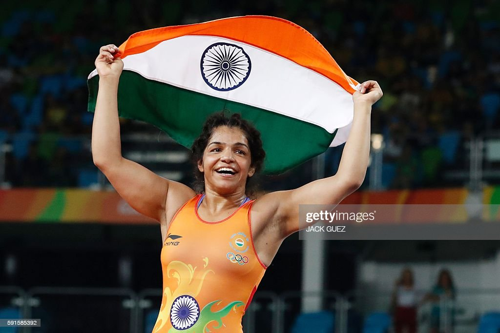 TOPSHOT - India's Sakshi Malik celebrates after winning against Kirghyzstan's Aisuluu Tynybekova in their women's 58kg freestyle bronze medal match on August 17, 2016, during the wrestling event of the Rio 2016 Olympic Games at the Carioca Arena 2 in Rio de Janeiro. / AFP / Jack GUEZ