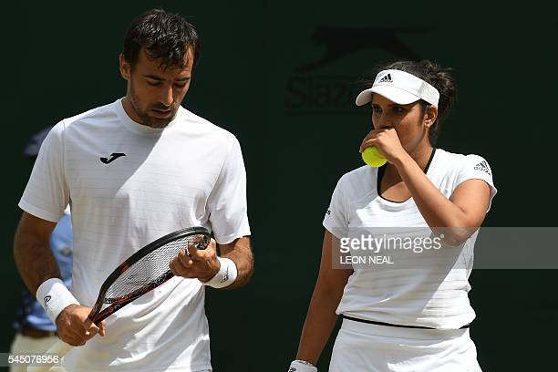 India's Sania Mirza and Croatia's Ivan Dodig play Britain's Neal Skupski and Anna Smith during a mixed doubles second round match on the ninth day of...