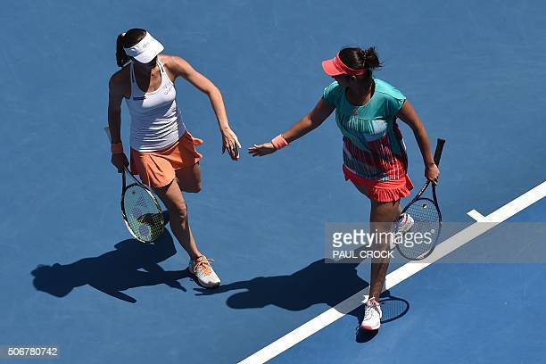 India's Sania Mirza and Switzerland's Martina Hingis speak between points during their women's doubles match against Germany's AnnaLena Groenefeld...