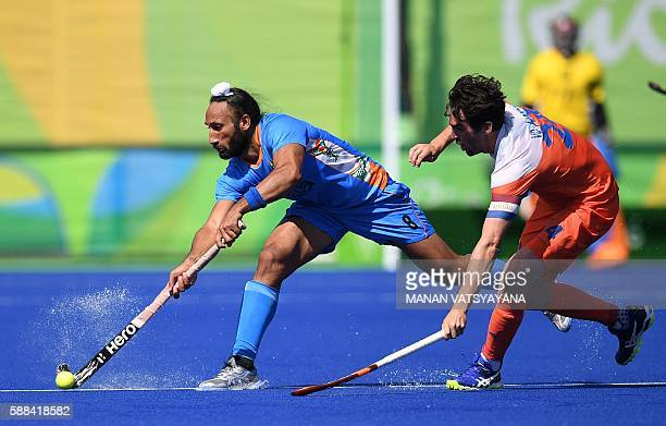 India's Sardar Singh hits the ball as Netherland's Robert van der Horst tries to stop him during the men's field hockey Netherland's vs India match...