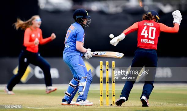 India's Shafali Verma chops the ball onto the stumps from England's bowler Sophie Ecclestone as wicketkeeper Amy Jones celebrates during their...
