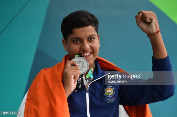 India's Shardul Vihan poses with his silver medal at the awards ceremony following the men's shooting double trap final at the 2018 Asian Games in...