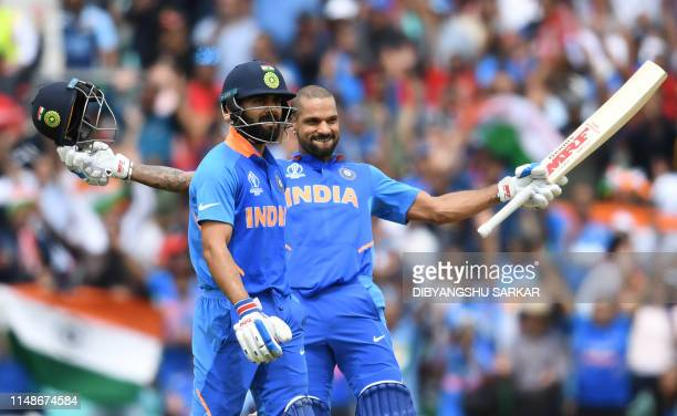 India's Shikhar Dhawan celebrates after scoring a century alongside India's captain Virat Kohliduring the 2019 Cricket World Cup group stage match...