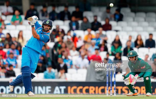 India's Shikhar Dhawan plays a shot for four runs during the ICC Champions Trophy Warmup cricket match between India and Bangladesh at The Oval in...