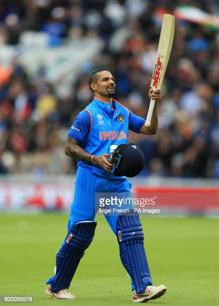 India's Shikhar Dhawan raises his bat to the crowd after his innings of 125