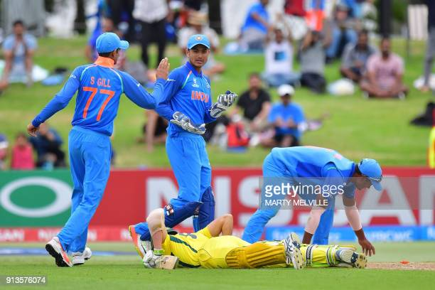 India's Shubman Gill keeper Harvik Desai and Anukul Roy celebrate Australia's Baxter J Holt being run out during the U19 World Cup cricket final...