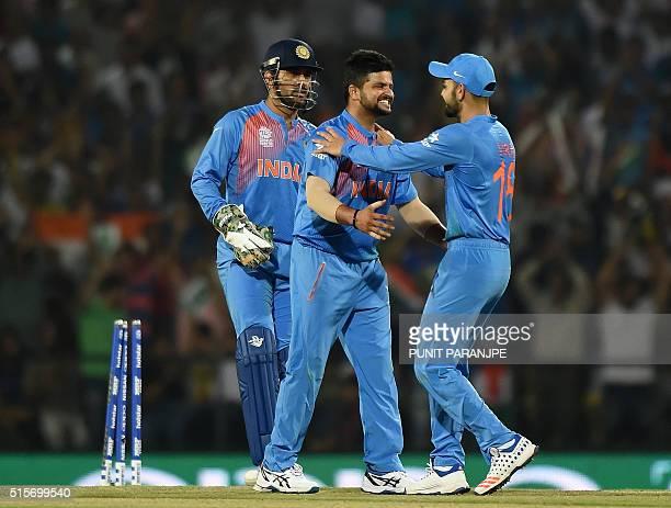 India's Suresh Raina celebrates with team mates Virat Kohli and captain Mahendra Singh Dhoni after the wicket of New Zealand batsman Kane Williamson...