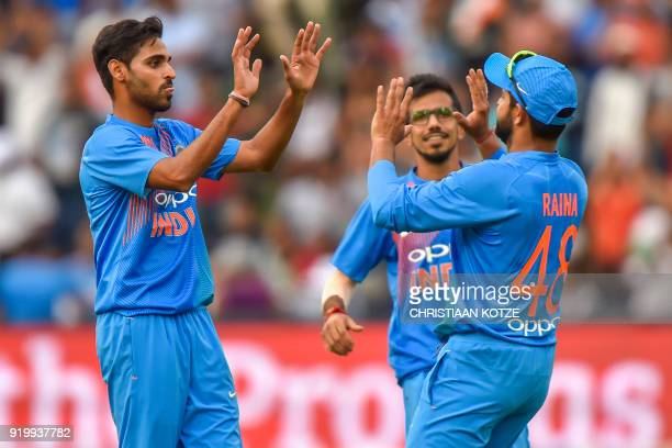 India's Suresh Raina celebrates with teammate Bhuvneshwar Kumar after taking a catch to dismiss unseen South African batsman Chris Morris during the...