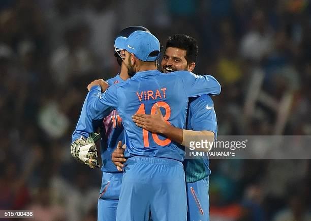 India's Suresh Raina celebrates with teammate Virat Kohli after the wicket of New Zealand batsman Kane Williamson during the World T20 cricket...