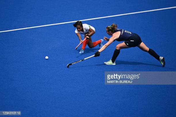 India's Sushila Chanu Pukhrambam strikes the ball past Ireland's Sarah Hawkshaw during their women's pool A match of the Tokyo 2020 Olympic Games...