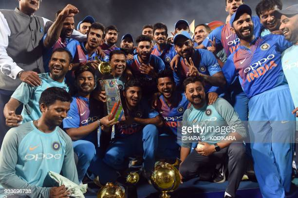 India's team members pose with the Nidahas Twenty20 TriSeries international cricket trophy at the end of the final Nidahas Twenty20 TriSeries...