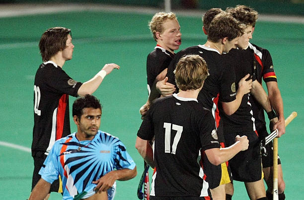 India`s Tushar Khandkar walks away dejected as German hockey players celebrate their third goal against India during the fournation Punjab Gold Cup...
