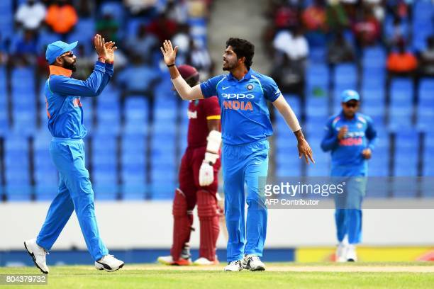 India's Umesh Yadav celebrates with captain Virat Kohli after bowling out West Indies' Evin Lewis during the third One Day International match...
