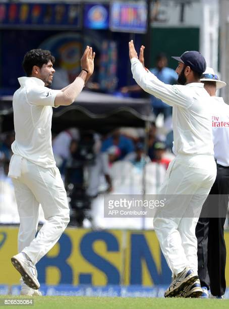 India's Umesh Yadav celebrates with his teammate Cheteshwar Pujara after he dismissed Sri Lanka's Kusal Mendis during the third day of the second...