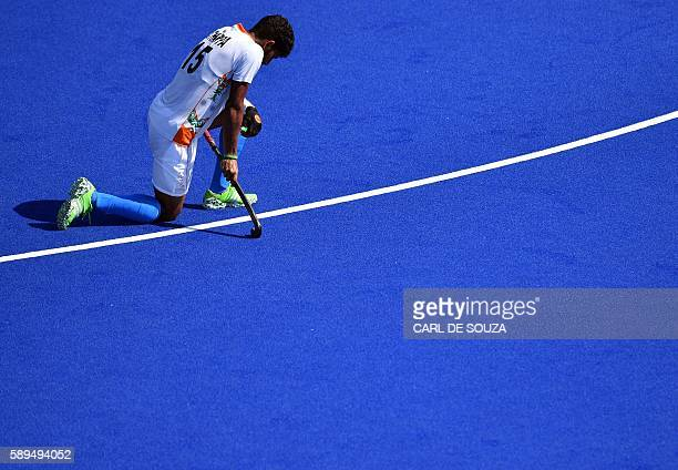 TOPSHOT India's Uthappa Sannuvanda kneels on the pitch at the end of the men's quarterfinal field hockey Belgium vs India match of the Rio 2016...