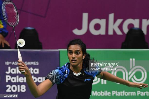 India's V Sindhu Pusarla hits a shot against Japans Akane Yamaguchi in their women's singles semifinal badminton match at the 2018 Asian Games in...