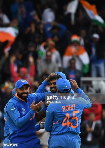 India's Vijay Shankar celebrates with India's captain Virat Kohli and teammates after the dismissal of Pakistan's ImamulHaq during the 2019 Cricket...