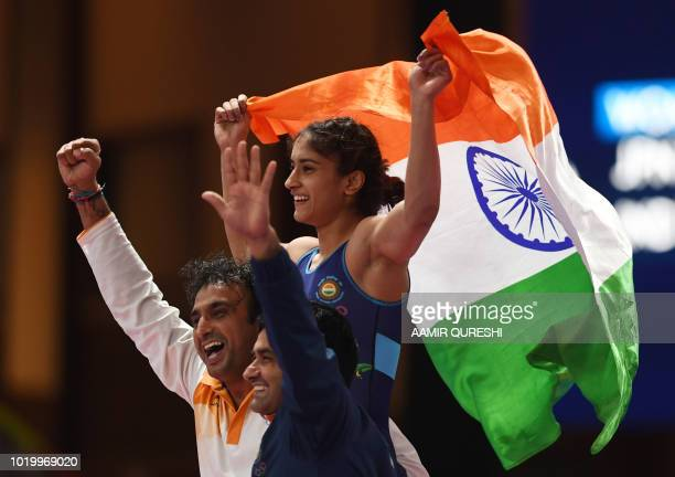 India's Vinesh holds up her national flag as she celebrates with his coach after beating Japan's Yuki Irie for the women's wrestling freestyle 50kg...