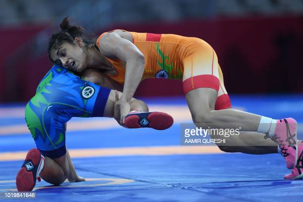 India's Vinesh Vinesh competes with Uzbekistan's Dauletbike Yakhshimuratova during the women's freestyle 50kg semifinal at the 2018 Asian Games in...