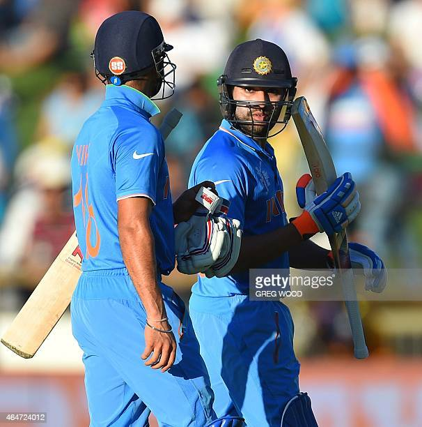 India's Virat Kohli and teammate Rohit Sharma leave the field at the tea break during the 2015 Cricket World Cup Pool B match between the United Arab...