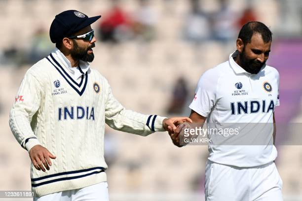 India's Virat Kohli hands India's Mohammed Shami the ball on the final day of the ICC World Test Championship Final between New Zealand and India at...