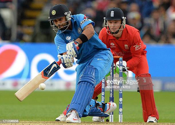 India's Virat Kohli hits a six as England wicketkeeper Jos Buttler looks on during the 2013 ICC Champions Trophy Final cricket match between England...