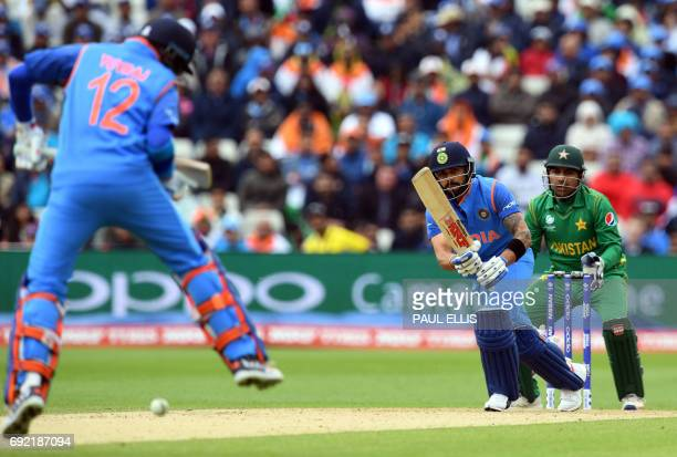 India's Virat Kohli jumps over a shot off the batting of teammate Yuvraj Singh during the ICC Champions trophy match between India and Pakistan at...