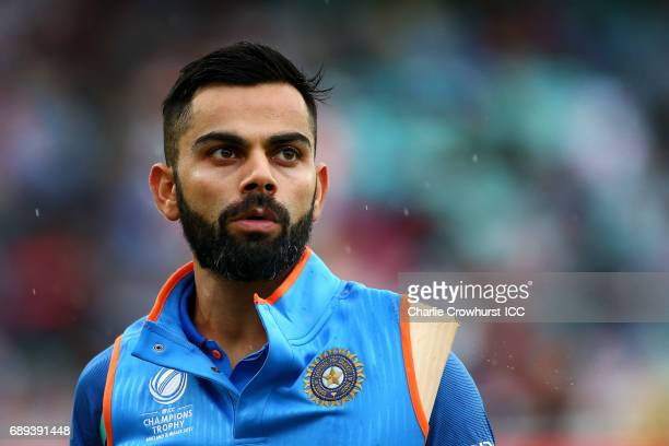 India's Virat Kohli keeps hit bat dry as the rain comes down during the ICC Champions Trophy Warmup match between India and New Zealand at The Kia...