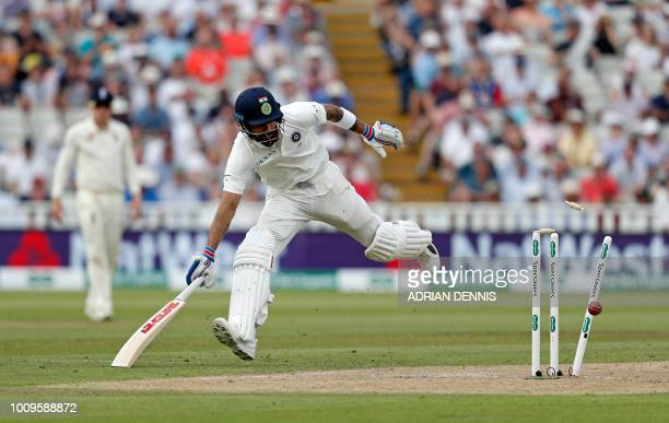 India's Virat Kohli safely runs back to the crease as the ball hits the stumps on the second day of the first Test cricket match between England and...