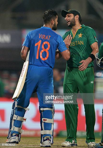 India's Virat Kohli shakes hand with Pakistan's captain Shahid Afridi as he celebrates after victory in the World T20 cricket tournament match...