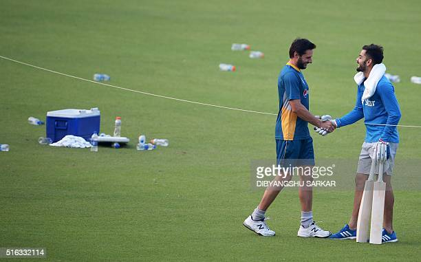 India's Virat Kohli shakes hands with Pakistan's captain Shahid Afridi during a training session at The Eden Gardens Cricket Stadium in Kolkata on...