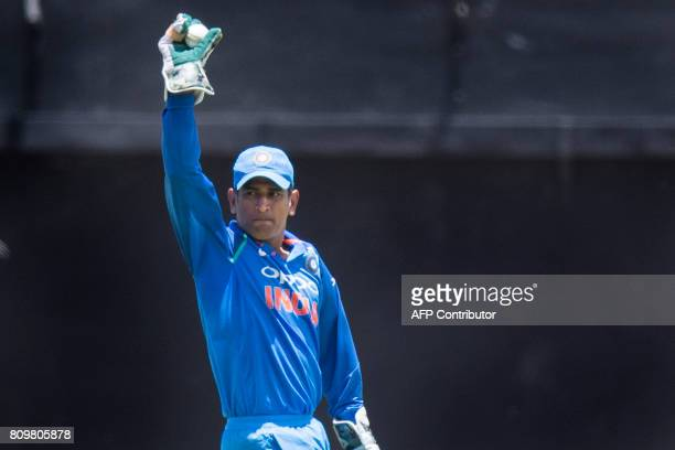 India's Wicket Keeper Mahindra Singh Dhoni holds up the ball after catching out West Indies' batsman Rovman Powell during the fifth One Day...