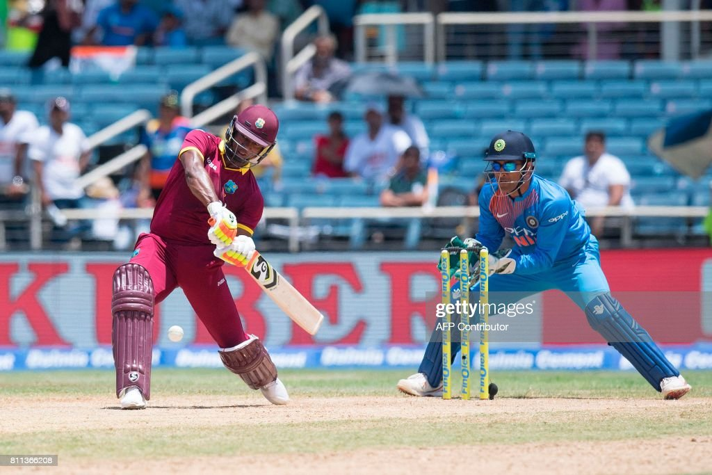 India's wicketkeeper MS Dhoni (R) fields as West Indies' Evin Lewis (L) plays a shot during the T20 match between West Indies and India at the Sabina Park Cricket Ground in Kingston, Jamaica, on July 9, 2017. /